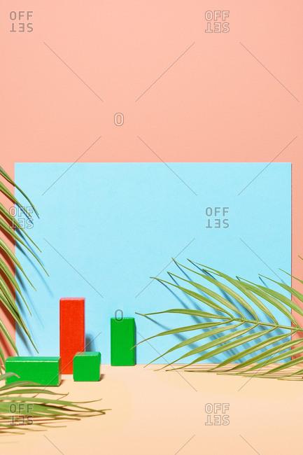 Studio shot of arrangement of Palm fern and wooden blocks on pastel background
