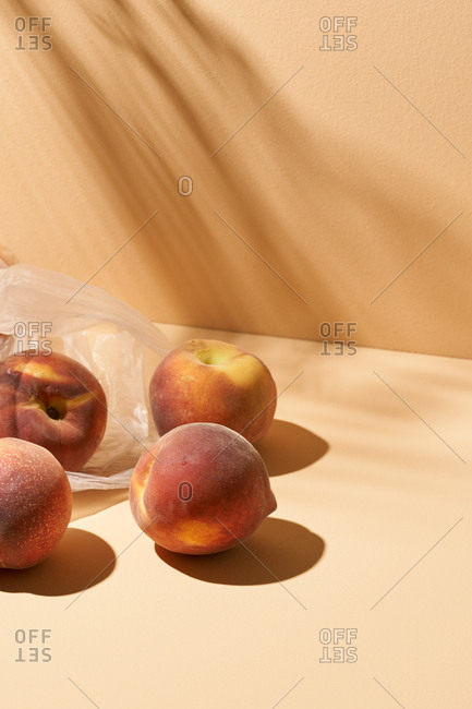 Studio shot of peaches and translucent plastic bag on peach background