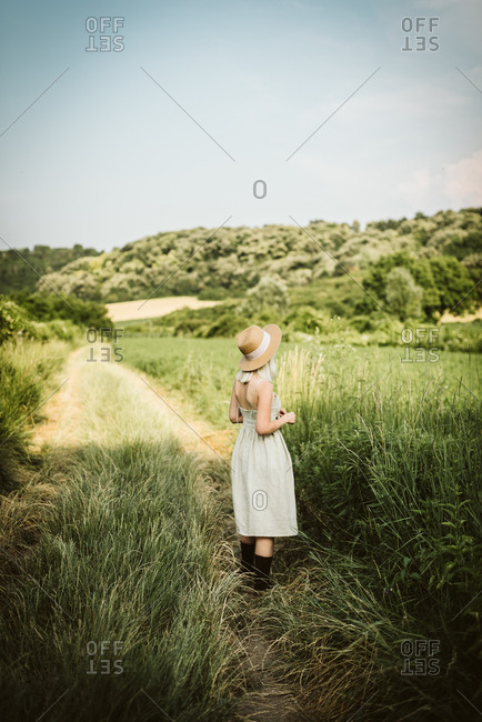 Blonde woman wearing sunhat standing in a rural field