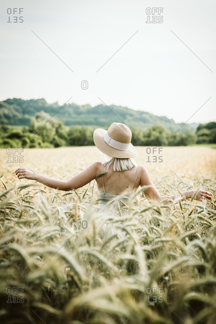 Blonde woman wearing sunhat standing in a wheat field