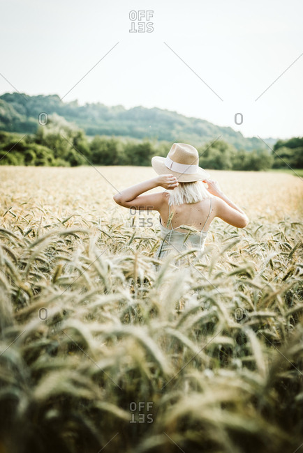 Woman wearing sunhat standing in a wheat field