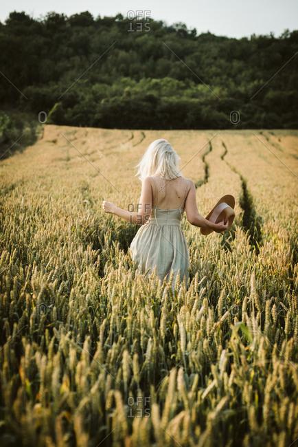 Blonde woman walking through a rye field
