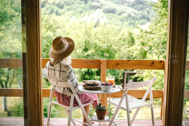 Woman sitting on deck eating breakfast