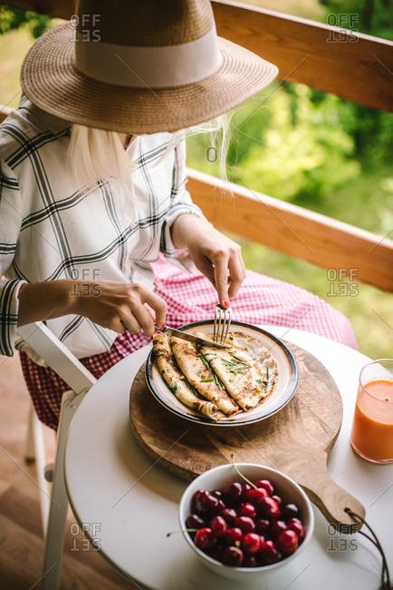 Woman eating breakfast on her balcony
