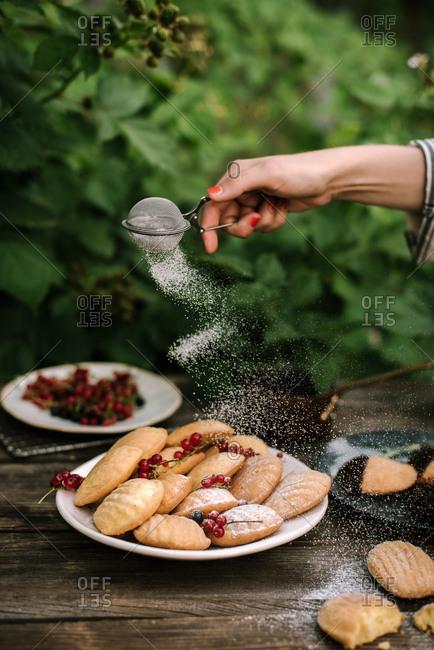 Woman sprinkling powdered sugar over Madeline cookies