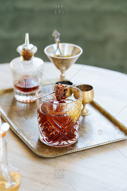 Cocktail garnished with a dried tomato on a serving tray