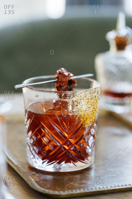 Cocktail garnished with a dried tomato on a vintage serving tray