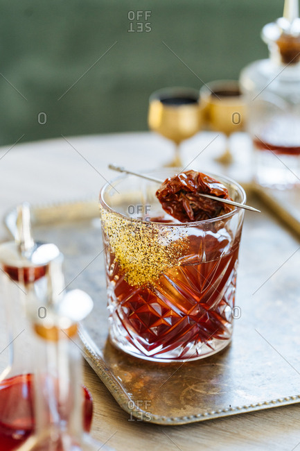 Mixed drink garnished with a dried tomato on a vintage serving tray