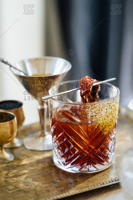 Mixed drink on a serving tray garnished with a dried tomato