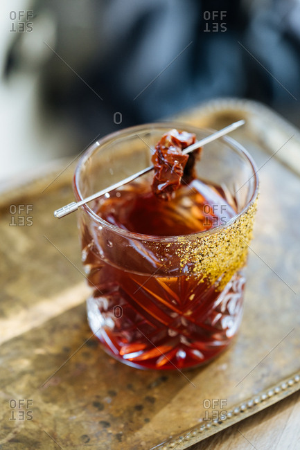 Mixed drink on a vintage serving tray garnished with a dried tomato