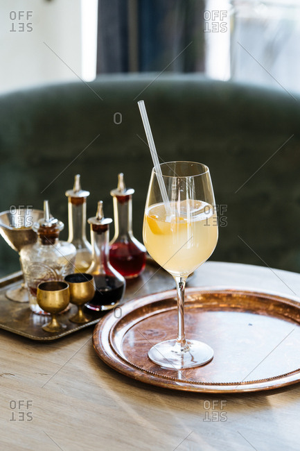 Yellow cocktail served with a straw on a vintage serving tray