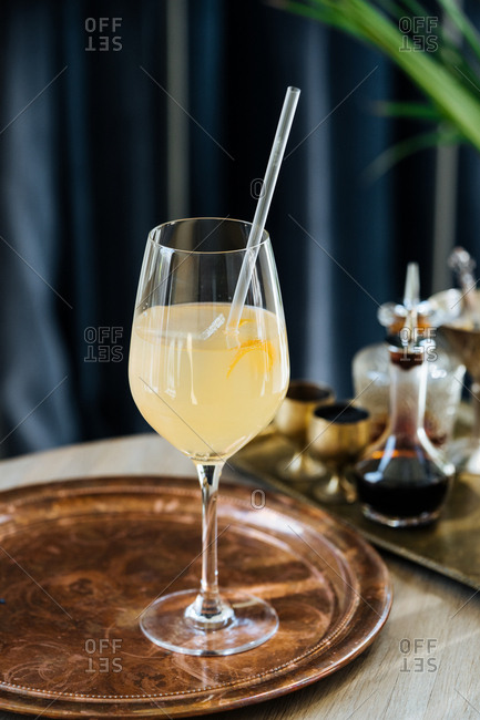 Yellow drink served with a straw on a vintage serving tray