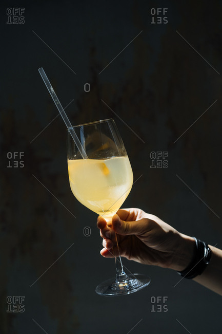 Hand holding a yellow cocktail with a straw