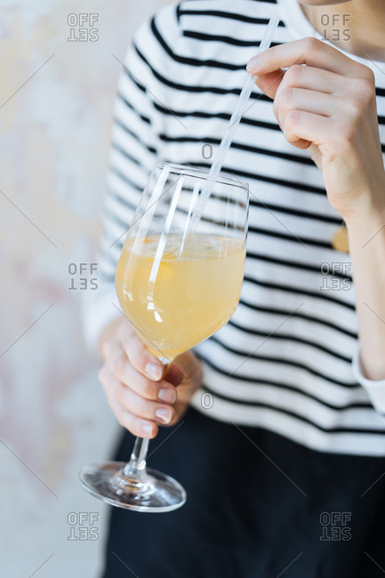 Woman drinking yellow cocktail with a straw
