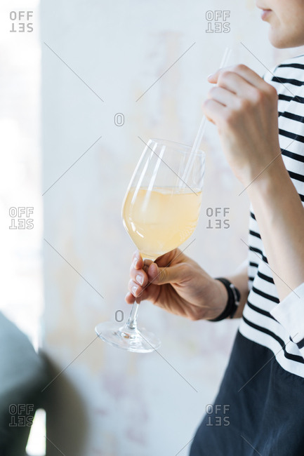 Woman drinking yellow cocktail in a wine glass with a straw