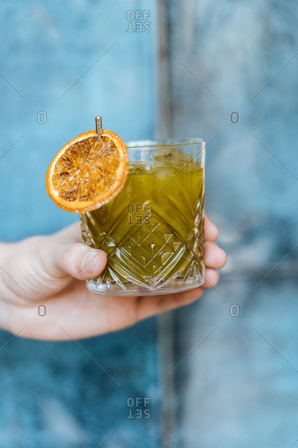 Hand holding a cocktail garnished with an orange