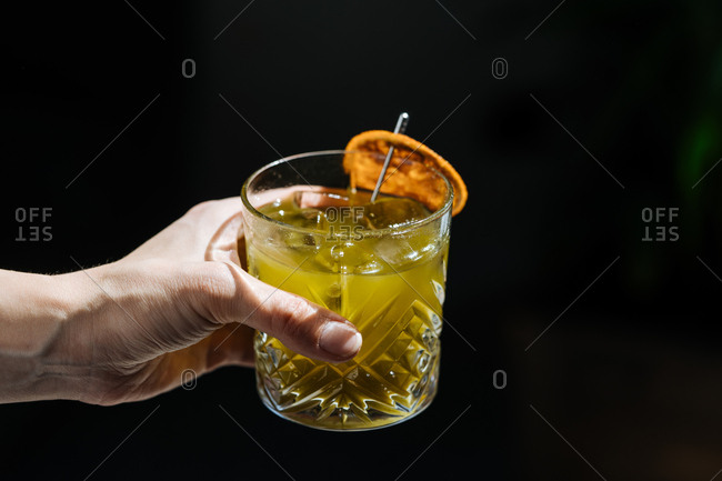 Hand holding a mixed drink garnished with an orange