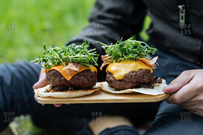 Man holding two large burgers