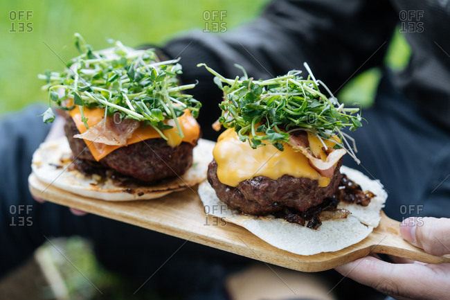 Two large burgers on a wooden board