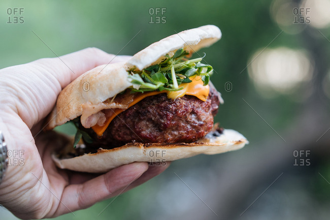 Hand holding a cheeseburger on a flatbread bun