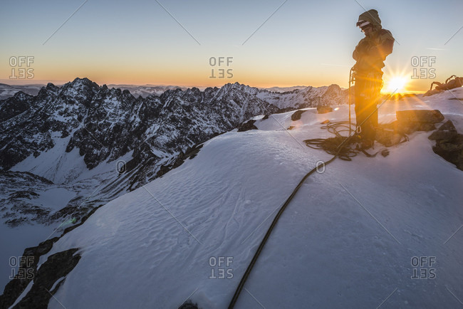 Climber standing on peak after finishing climbing route at sunset, Mieguszowiecki Szczyt Wielki, Tatra Mountains, Malopolskie Voivodeship, Poland