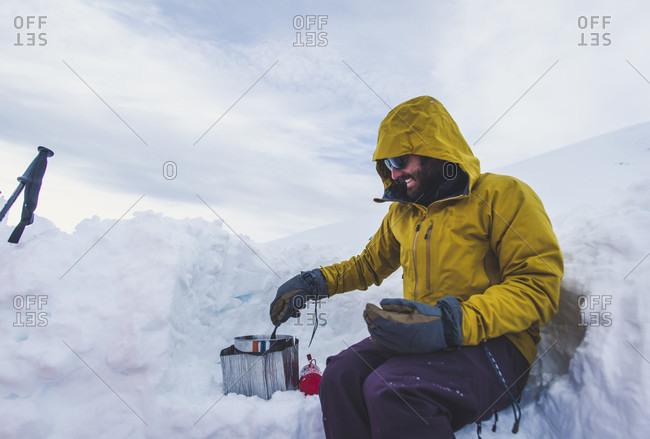 Man boiling water while climbing Mt Shasta, California, USA