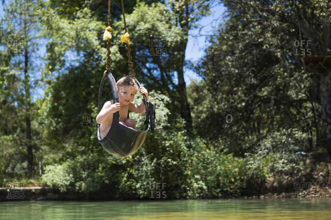 Boy riding zip line over water, Rancho Santa Elena, Hidalgo, Mexico