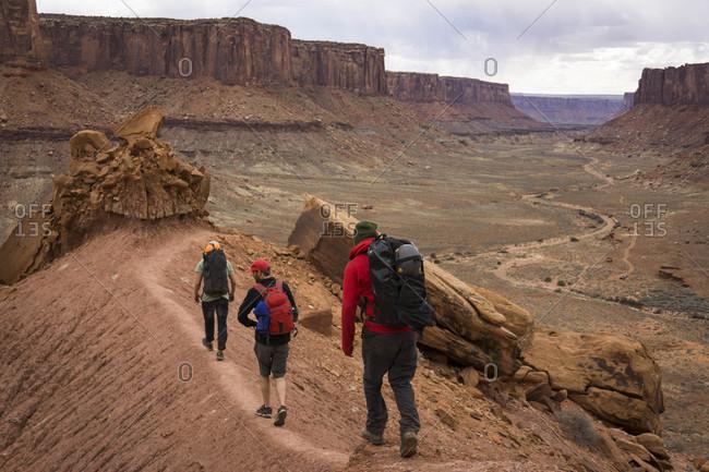 Three men hiking in Canyonlands National Park, Moab, Utah, USA