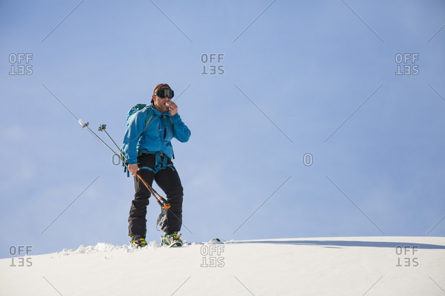 Cross-country skier eating a chunk of snow in North Cascades National Park, Washington State, USA