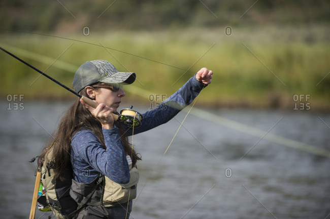 Woman fishing in river, Colorado, USA