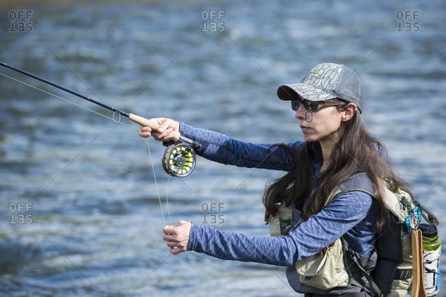 Woman fishing in river, Colorado, USA
