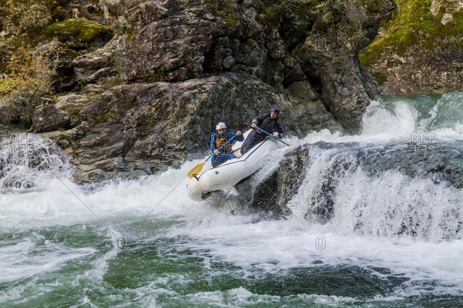 Two men rafting down waterfall on Little North Santiam River, Opal Creek Wilderness, Oregon, USA