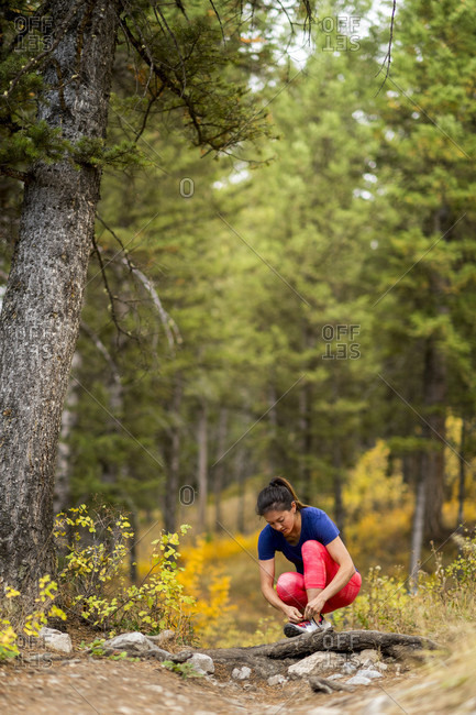 Woman tying shoes while trail running