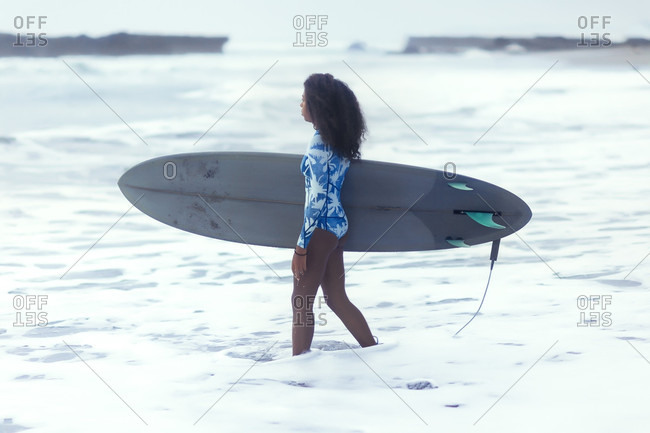 Woman with surfboard in sea