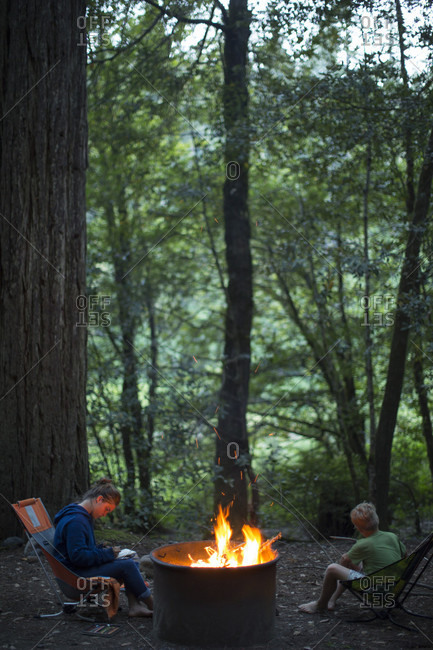 Two kids hanging out by the campfire at a campground
