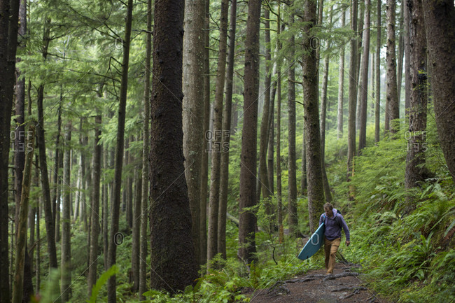 Surfer waking with his board and backpack through coastal forest en route to the beach