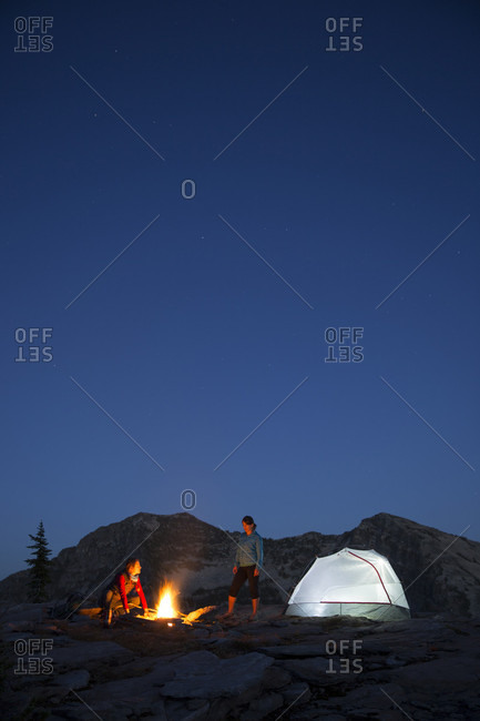 Two adult women standing next to their tent and campfire at night while on an overnight backpacking trip