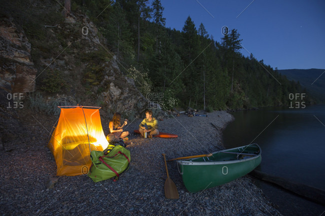 Adult couple enjoying nightlife and their camping scene while on an  overnight canoe trip
