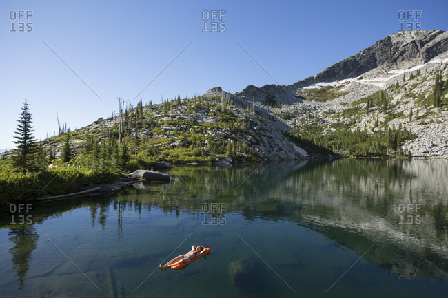 Adult woman in a swimsuit sunbathing on her inflatable camping mattress in the middle of a cold high mountain lake