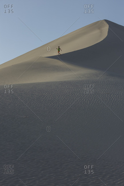 Boy age 10 running down sand dunes