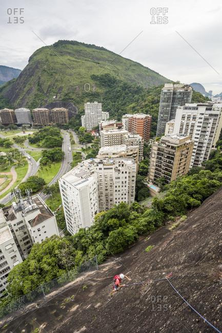 Man rock climbing Morro do Cantagalo (Cantagalo Mountain), Rio de Janeiro, Brazil