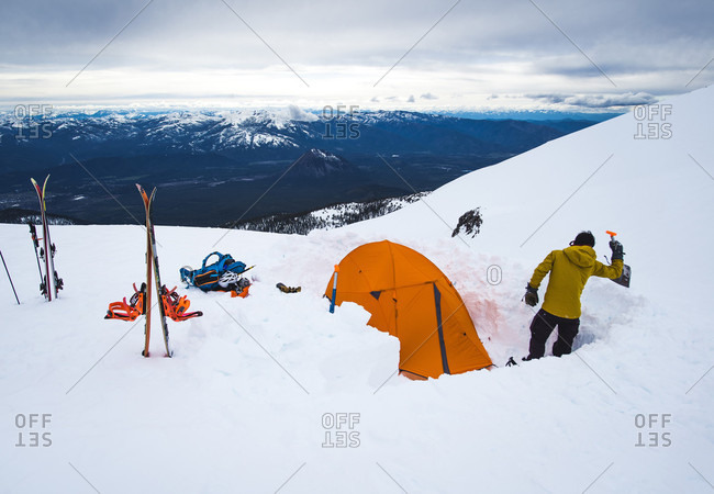 Man camping with tent in winter at Mt Shasta, California, USA