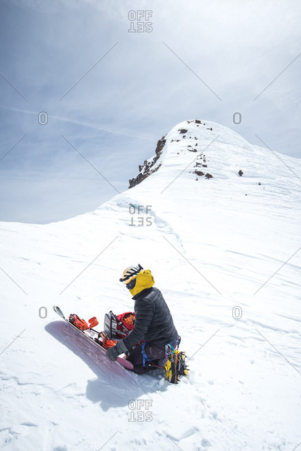 Man assembling snowboard before descending Mt Shasta, California, USA