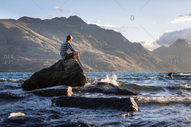 Man sitting on rock in Lake Wakatipu, Otago, New Zealand