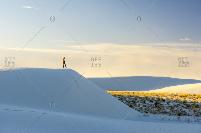 Girl standing on top of sand dune, Alamagordo, New Mexico, USA