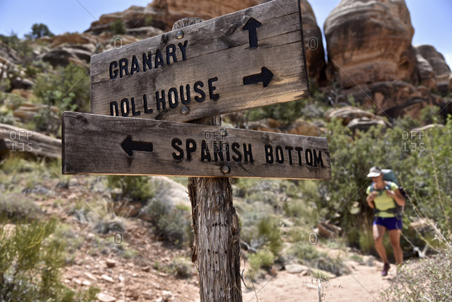 Trail sign directing female hiker in Canyonlands National Park, Moab, Utah, USA