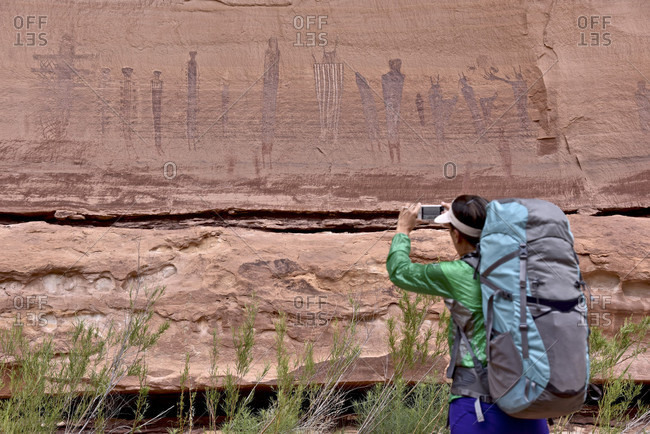Backpacker taking photo of Harvest Scene petroglyphs in The Maze section of Canyonlands National Park, Moab, Utah, USA