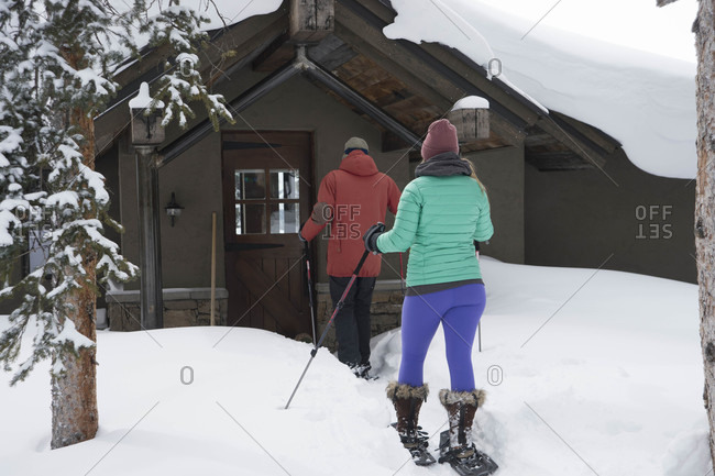 Couple arriving at mountain cabin on snowshoes, Aspen, Colorado, USA