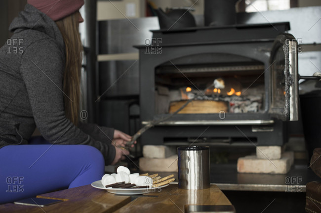 Woman roasting marshmallows for smores in stove