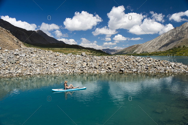 Aerial view of young female relaxing on paddle board on high alpine lake in Colorado, USA